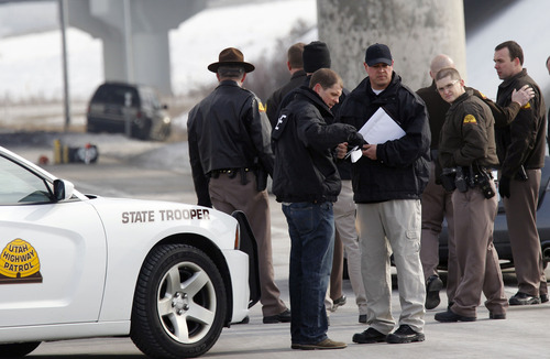 Al Hartmann  |  The Salt Lake Tribune Utah Highway Patrol troopers investigate SUV, in rear, in an apparent murder-suicide near the Redwood Road exit on eastbound I-80 Friday February 8.