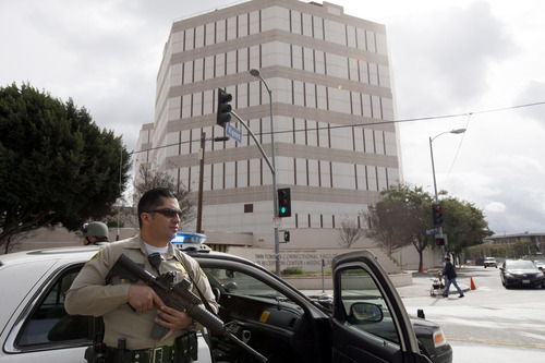 A Los Angeles County Sheriff's deputy stands alert outside the Twin Towers jail, background, which was put on lockdown after an alleged  sighting of suspect Christopher Jordan Dorner Friday Feb. 8, 2013 in Los Angeles. The lockdown was later lifted. Law enforcement officers worked through the night amid an incoming snow storm searching for the former Los Angeles police officer accused of carrying out a killing spree because he felt he was unfairly fired from his job.  (AP Photo/Nick Ut)