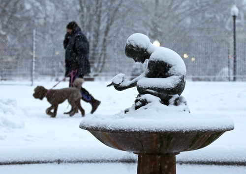 "A man walks his dog past the snow covered ""Boy and Bird"" fountain in the Boston Public Garden in Boston, Friday, Feb. 8, 2013. Mass. Gov. Deval Patrick declared a state of emergency Friday and banned travel on roads as of 4 p.m. as a blizzard that could bring nearly 3 feet of snow to the region began to intensify. As the storm gains strength, it will bring ""extremely dangerous conditions"" with bands of snow dropping up to 2 to 3 inches per hour at the height of the blizzard, Patrick said. (AP Photo/Charles Krupa)"