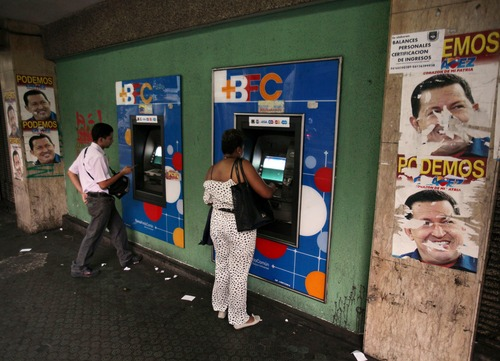 People withdraw money from cash machines where election propaganda supporting Venezuela's President Hugo Chavez cover the nearby walls in Caracas, Venezuela, Friday, Feb. 8, 2013. Venezuela's government announced Friday that it is devaluing the country's currency, a long-anticipated change expected to push up prices in the heavily import-reliant economy. Officials said the fixed exchange rate is changing from 4.30 bolivars to the dollar to 6.30 bolivars to the dollar. Venezuela's government has had strict currency exchange controls since 2003 and maintains a fixed, government-set exchange rate. While those controls have restricted the amounts of dollars available at the official rate, an illegal black market has flourished and the value of the bolivar has recently been eroding. (AP Photo/Fernando Llano)