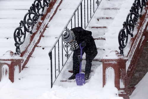A woman cleans the steps in front of her building in the South Boston neighborhood of Boston,  Saturday, Feb. 9, 2013. (AP Photo/Gene J. Puskar)