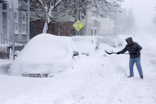 A man shovels out a car on Third street in the South Boston neighborhood of Boston, Saturday, Feb. 9, 2013. (AP Photo/Gene J. Puskar)