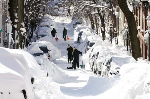 Shovelers pause for a picture while digging out their car in Boston, Sunday, Feb.10, 2013. (AP Photo/Winslow Townson)