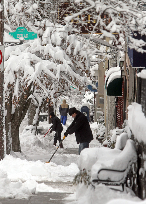 Shop owners clear the sidewalk in front of their stores on Main St. in Irvington, N.Y., Saturday, Feb. 9, 2013. The year's first major winter storm dumped up to 21 inches on the Lower Hudson Valley.  (AP Photo/The Journal News, Seth Harrison) NYC OUT, NO SALES, ONLINE OUT, TV OUT, NEWSDAY INTERNET OUT; MAGS OUT