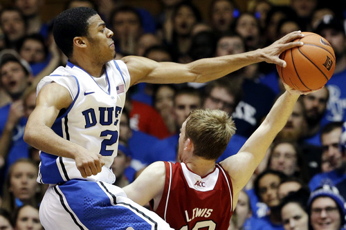 Duke's Quinn Cook (2) blocks a shot by North Carolina State's Tyler Lewis during the second half of an NCAA college basketball game in Durham, N.C., Thursday, Feb. 7, 2013. Duke won 98-85. (AP Photo/Gerry Broome)