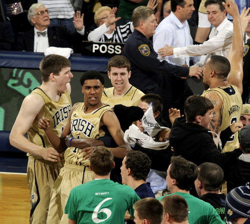 Notre Dame players including Cameron Biedscheid (1) and Zach Auguste (2) celebrate with fans following their 104-101 win against Louisville in the fifth overtime of their NCAA college basketball game, Saturday, Feb. 9, 2013, in South Bend, Ind. At top right, Louisville head coach Rick Pitino shakes hands with Notre Dame head coach Mike Brey. (AP Photo/Joe Raymond)