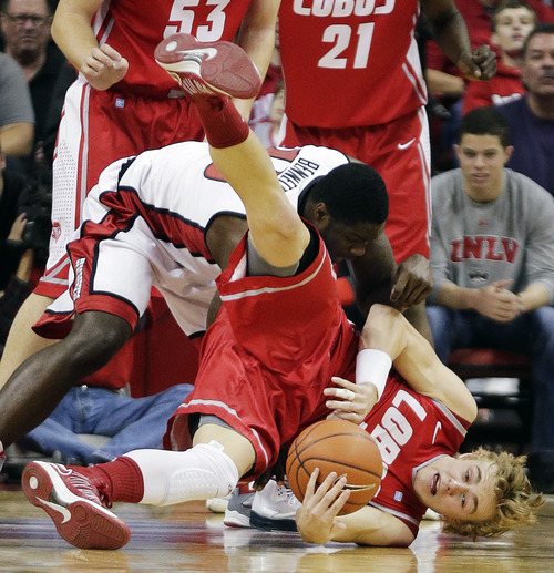 New Mexico's Hugh Greenwood, bottom, falls to the court as he scrambles for a loose ball against UNLV's Anthony Bennett (15) in the first half of an NCAA college basketball game, Saturday, Feb. 9, 2013, in Las Vegas. (AP Photo/Julie Jacobson)