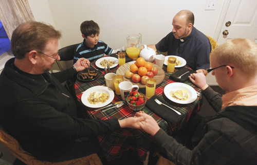 Al Hartmann  |  The Salt Lake Tribune Mark Dexheimer-Trujillo, left, Dillan Whitlock, 8, the Rev. Robert Trujillo and Jordan Kersey, 20, pray before breakfast Friday February 8 before another day of work and school. Trujillo can legally marry people but can't marry Mark, his longtime partner. Together they have raised seven children.