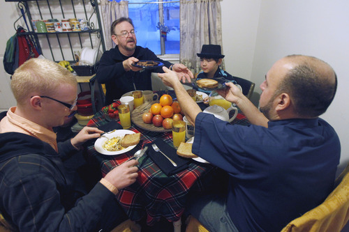 Al Hartmann  |  The Salt Lake Tribune Mark Dexheimer-Trujillo, top, passes food to his partner, the Rev. Robert Trujillo, right. Their two children Jordan Kersey, 20, left, and Dillan Whitlock, 8, eat breakfast with them Friday February 8 before another day of work and school. Trujillo can legally marry people but can't get married himself to his longtime partner, Mark. Together they have raised seven children.