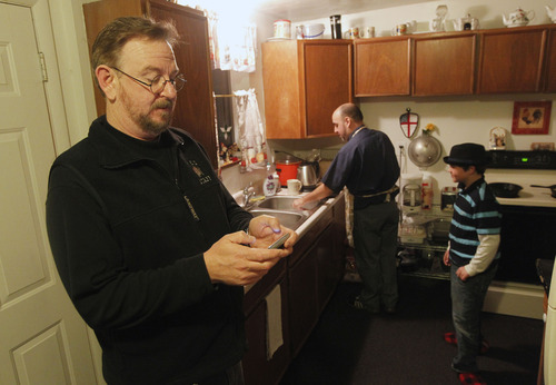 Al Hartmann  |  The Salt Lake Tribune Mark Dexheimer-Trujillo, left, checks his phone messages as his partner. the Rev. Robb Trujillo, gets breakfast going as their son Dillan Whitlock, 8 looks on. Trujillo can legally marry people but can't get married himself to his longtime partner, Mark, who together, have raised seven children.