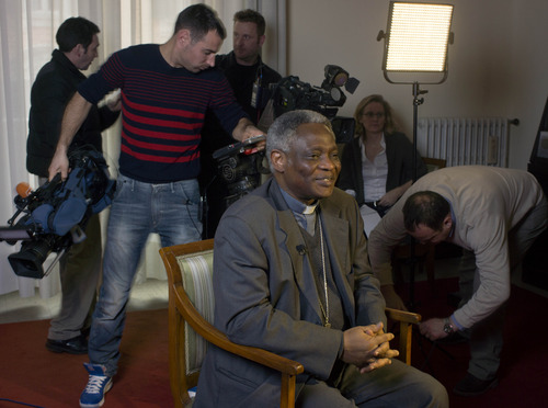 ADD FEB. 12 - TV crews set up their equipment as Ghanaian Cardinal Peter Kodwo Appiah Turkson waits to be interviewed, in Rome, Tuesday, Feb. 12, 2013. One of Africa's brightest hopes to be the next pope, Ghanaian Cardinal Turkson, says the time is right for a pontiff from the developing world. In the background is a painting of late Pope John Paul II.  (AP Photo/Domenico Stinellis)
