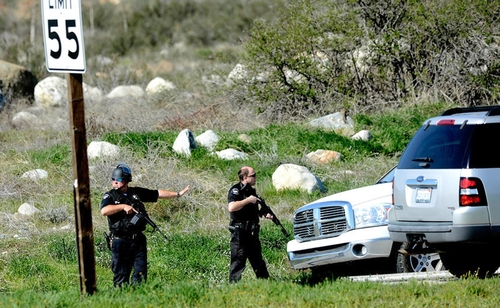 Redlands Police officers man a blockade  near the entrance to the San Bernardino National Forest after a fugitive ex-Los Angeles cop sought in three killings engaged in a shootout with authorities that wounded two officers in the San Bernardino Mountains near Big Bear Lake, Tuesday, Feb. 12, 2013. (AP Photo/The Sun, Gabriel Luis Acosta)  VENTURA COUNTY STAR OUT; RIVERSIDE PRESS-ENTERPRISE OUT; THE VICTOR VALLEY DAILY PRESS OUT