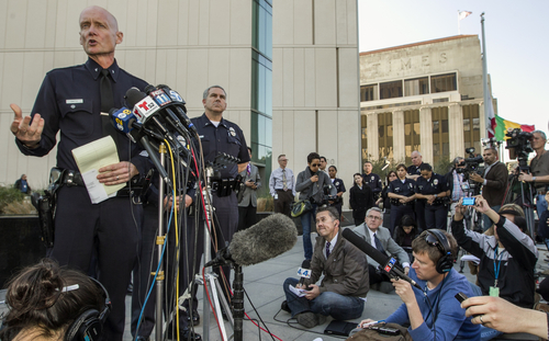 Los Angeles Police Commander Andrew Smith, left, briefs the media about the shootout scene in Big Bear that allegedly involves triple-murder suspect Christopher Jordan Dorner, during a news conference in front of the Police Administration Building in Los Angeles Tuesday, Feb. 12, 2013. (AP Photo/Damian Dovarganes)
