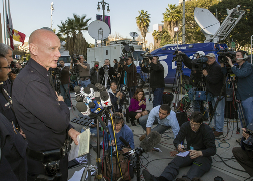 Los Angeles Police Commander Andrew Smith, left, briefs the media about Christopher Jordan Dorner, during a news conference in front of the Police Administration Building in Los Angeles, Tuesday, Feb. 12, 2013. Dorner, a man police believe to be the fugitive ex-Los Angeles officer wanted in three killings was barricaded inside a burning cabin Tuesday after a shootout in a California mountain town that left one deputy dead and another wounded. (AP Photo/Damian Dovarganes)