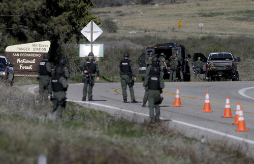 Law Enforcement personnel gear up along Hwy 38 during the hunt for accused killer and fired Los Angeles police officer, Christopher Dorner in Yacaipa, Caif.,Tuesday, Feb. 12, 2013. Dorner, a man police believe to be the fugitive ex-Los Angeles officer wanted in three killings, was barricaded inside a burning cabin Tuesday after a shootout in a California mountain town that left one deputy dead and another wounded. (AP Photo/Chris Carlson)