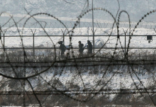 South Korean army soldiers patrol along a barbed-wire fence near the demilitarized zone of Panmunjom in Paju, South Korea, Sunday, Feb. 10, 2013. Without confirmation of when North Korea might carry out its vow to conduct its third nuclear test, the building suspense has prompted outsiders to look at dates Pyongyang has chosen for past atomic tests and rocket and missile launches. (AP Photo/Ahn Young-joon)