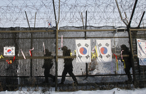 South Korean army soldiers patrol along a barbed-wire fence at the Imjingak Pavilion, near the demilitarized zone of Panmunjom, in Paju, South Korea, Sunday, Feb. 10, 2013.  Without confirmation of when North Korea might carry out its vow to conduct its third nuclear test, the building suspense has prompted outsiders to look at dates Pyongyang has chosen for past atomic tests and rocket and missile launches. (AP Photo/Ahn Young-joon)