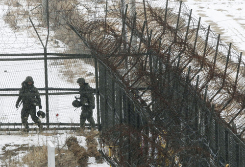 South Korean army soldiers patrol along a barbed-wire fence at the Imjingak Pavilion, near the demilitarized zone of Panmunjom, in Paju, South Korea, Tuesday, Feb. 12, 2013. South Korea is confirming that North Korea has tested a nuclear device in defiance of U.N. orders to stop building atomic weapons.(AP Photo/Ahn Young-joon)