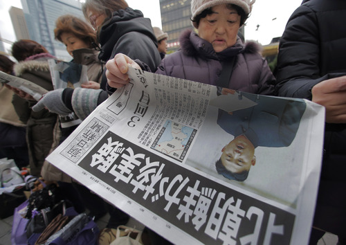 "A woman reads a delivered extra edition of a Japanese newspaper reporting North Korea's nuclear test, in Tokyo Tuesday, Feb. 12, 2013. North Korea said it successfully detonated a miniaturized nuclear device at a northeastern test site Tuesday, defying U.N. Security Council orders to shut down atomic activity or face more sanctions and international isolation. The extra carrying a photo of North Korean leader Kim Jong Un reads: ""North Korea conducted a nuclear test."" (AP Photo/Itsuo Inouye)"