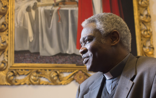 Ghanaian Cardinal Peter Kodwo Appiah Turkson talks to the Associated Press during an interview, in Rome, Tuesday, Feb. 2013. One of Africa's brightest hopes to be the next pope, Ghanaian Cardinal Turkson, says the time is right for a pontiff from the developing world. In the background is a painting of late Pope John Paul II.  (AP Photo/Domenico Stinellis)