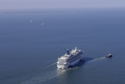 A disabled Carnival Lines cruise ship is towed to harbor off Mobile Bay, Ala., Thursday, Feb. 14, 2013.  The ship with over 1,000 passengers aboard has been idled for nearly a week in the Gulf of Mexico following an engine room fire. (AP Photo/Gerald Herbert)