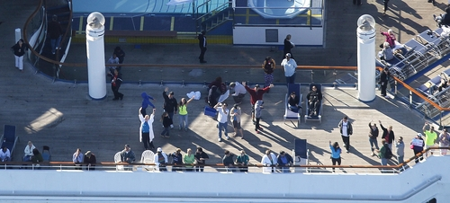 In this aerial photo, passengers congregate on an upper deck of the disabled Carnival Lines cruise ship Triumph as it is towed to harbor off Mobile Bay, Ala., Thursday, Feb. 14, 2013. The ship with more than 4,200 passengers and crew members has been idled for nearly a week in the Gulf of Mexico following an engine room fire. (AP Photo/Gerald Herbert)