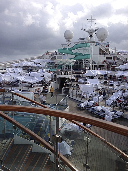 In this Sunday, Feb. 10, 2013 photo, provided by Kalin Hill of Houston, passengers with makeshift tents are seen on the the deck of the Carnival Triumph cruise ship at sea in the Gulf of Mexico. The ship nearing Mobile Bay is without engine power and is being towed by tugboats. (AP Photo/Kalin Hill)