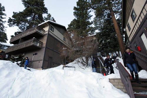 Members of the news media are shown outside a home, at left, in Big Bear, Calif., where the owners of the cabin were taken hostage by fugitive Christopher Dorner. Police scoured mountain peaks for days, using everything from bloodhounds to high-tech helicopters in their manhunt for Dorner, a revenge-seeking ex-cop. They had no idea he was hiding among them, possibly holed up in this vacation home across the street from their command post.     (AP Photo/Nick Ut)