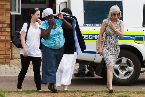 Sister of Olympic athlete Oscar Pistorius, Aimee, left, leaves the Mamelodi Hospital, east of Pretoria, South Africa, with unidentified persons, Thursday, Feb. 14, 2013 where she visited her brother while he was being examined. Pistorius was taken into custody after a 30-year-old woman, Reeva Steenkamp, was shot dead at his home. (AP Photo/Walso Swiegers)