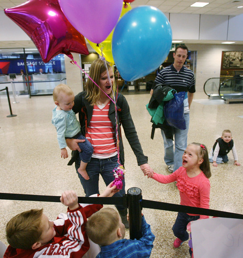 Steve Griffin  |  The Salt Lake Tribune Jaymi Bonner, right, smiles as she gets a look at all of her new cousins holding balloons at the main terminal at the Salt Lake City International Airport in Salt Lake City, Utah Thursday, February 14, 2013. Jaymi and her mother, Jeana Bonner, left, holding her baby daughter, Bryne, arrived home after weeks spent in Russia trying to finalize the adoption of 5-year-old Jaymi, who has Down syndrome. Jaymi's father, Wayne, is in the background. The Russian government in January approved a ban on adoptions by U.S. citizens, but agreed to let adoptions that were already basically completed to proceed. This was one of about 50 adoptions allowed to move forward.