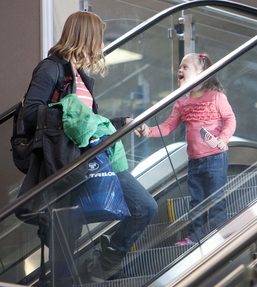 Steve Griffin  |  The Salt Lake Tribune Jaymi Bonner smiles at her mother, Jeana Bonner, as she gets a look at all of her new family members as she rides the escalator down to the main terminal at the Salt Lake City International Airport in Salt Lake City, Utah Thursday, February 14, 2013. The Bonners arrived home today after weeks spent in Russia trying to finalize the adoption of 5-year-old Jaymi, who has Down syndrome. The Russian government in January approved a ban on adoptions by U.S. citizens, but agreed to let adoptions that were already basically completed to proceed. This was one of about 50 adoptions allowed to move forward.