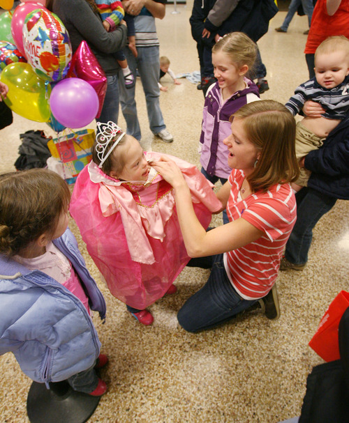 Steve Griffin  |  The Salt Lake Tribune Jeana Bonner helps her daughter Jaymi Bonner put on a princess dress at the main terminal at the Salt Lake City International Airport in Salt Lake City, Utah Thursday, February 14, 2013. The mother and daugher arrived home today after weeks spent in Russia trying to finalize the adoption of 5-year-old Jaymi, who has Down syndrome. The Russian government in January approved a ban on adoptions by U.S. citizens, but agreed to let adoptions that were already basically completed to proceed. This was one of about 50 adoptions allowed to move forward.