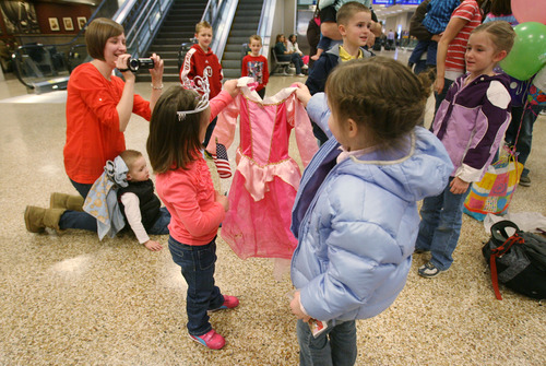 Steve Griffin  |  The Salt Lake Tribune Jaymi Bonner, center, and her new cousin, Jackie Rasmussen, hold up a princess dress at the main terminal at the Salt Lake City International Airport in Salt Lake City, Utah Thursday, February 14, 2013. Jaymi and her mother, Jeana Bonner, arrived home after weeks spent in Russia trying to finalize the adoption of 5-year-old Jaymi, who has Down syndrome. The Russian government in January approved a ban on adoptions by U.S. citizens, but agreed to let adoptions that were already basically completed to proceed. This was one of about 50 adoptions allowed to move forward.