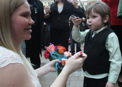 Rick Egan  |  The Salt Lake Tribune  Sarha Gonzales shares her wedding cake with her 4-year-old son, Anthony, after being married on the Ferris wheel at Scheels by Murray Mayor Dan Snarr Thursday, February 14, 2013.