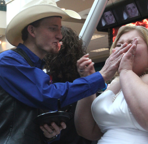 Rick Egan  |  The Salt Lake Tribune  Kelli Silcox gets a face full of wedding cake from her new husband, James Bytendorp, after being married by Murray Mayor Dan Snarr while riding the Ferris wheel at Scheels on Thursday.