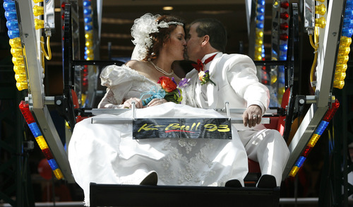 Rick Egan  |  The Salt Lake Tribune  Angela and James Parks kiss on the Ferris wheel at Scheelsin Sandy. The couple were one of 16 married while riding the Ferris wheel on Valentine's Day. The free Valentine's Day wedding was sponsored by radio station K-Bull 93.