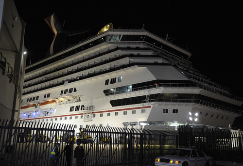 Tight security surrounds the Carnival Triumph after it docked in Mobile, Ala., Thursday, Feb. 14, 2013. The ship with more than 4,200 passengers and crew members has been idled for nearly a week in the Gulf of Mexico following an engine room fire. (AP Photo/G M Andrews)