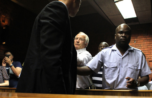 Olympic athlete Oscar Pistorius's father Henke Pistorius, center, gestures to his son as is lead by police officer out of the witness bench after his bail application appearance at the magistrate court in Pretoria, South Africa, Friday, Feb. 15, 2013. Pistorius was taken into custody after a 30-year-old woman, Reeva Steenkamp, was shot dead at his home on Thursday, Feb. 14, 2013. (AP Photo/Themba Hadebe)