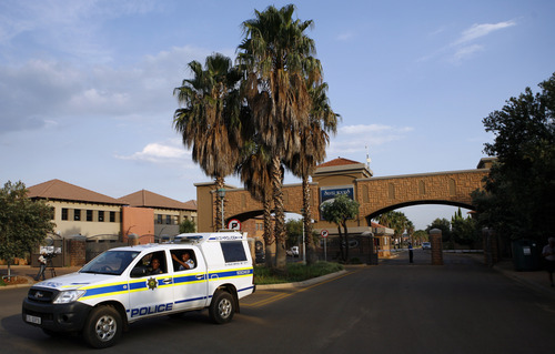 A police vehicle leaves the housing estate where Olympian Oscar Pistorius lives in Pretoria, South Africa, Thursday, Feb. 14, 2013. Pistorius was charged Thursday with the murder of his girlfriend who was shot inside his home in South Africa, a stunning development in the life of a national hero known as the Blade Runner for his high-tech artificial legs. (AP Photo/Themba Hadebe)