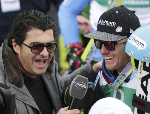 Former Italian skier Alberto Tomba, left, interviews United States's Ted Ligety after Ligety won the gold medal of the men's giant slalom at the Alpine skiing world championships in Schladming, Austria, Friday, Feb.15,2013. (AP Photo/Matthias Schrader)