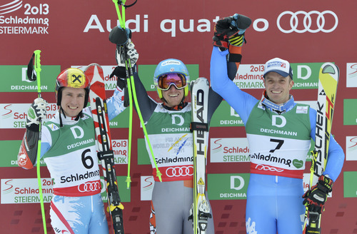 United States's gold medal winner Ted Ligety is flanked by silver medal winner Slovakia's Adam Zampa, left, and Italy's bronze medalist Manfred Moelgg after the second run of the men's giant slalom at the Alpine skiing world championships in Schladming, Austria, Friday, Feb. 15, 2013. (AP Photo/Kerstin Joensson)