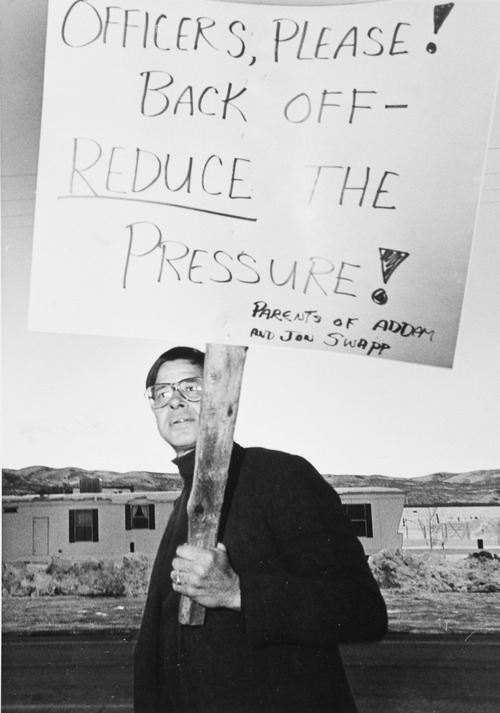 Tribune file photo by Rick Egan  Ramon Swapp, father of Addam and Jonathan Swapp, carries a sign at the staging center in Marion, Utah.