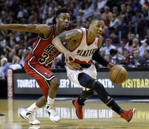 Portland Trail Blazers' Damian Lillard (0) drives against Miami Heat's Norris Cole (30) during the second half of an NBA basketball game in Miami, Tuesday, Feb. 12, 2013. The Heat won 117-104. (AP Photo/Alan Diaz)