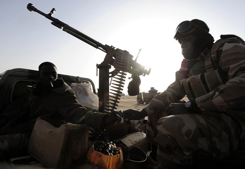 Malian soldiers sit aboard a vehicle as they near Bourem, northern Mali, Sunday, Feb. 17, 2013. Mali's military detained eight Arab men last week in Timbuktu, raising fears of further reprisals against the region's Arab minority whose members are accused of having supported the al-Qaida-linked groups which overran northern Mali last year. (AP Photo /Pascal Guyot, Pool)