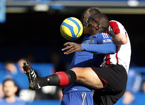 Chelsea's Demba Ba, centre, competes for the ball with Brentford's Tony Craig during the English FA Cup fourth round replay soccer match between Chelsea and Brentford at Stamford Bridge stadium in London, Sunday, Feb. 17, 2013.  (AP Photo/Matt Dunham)