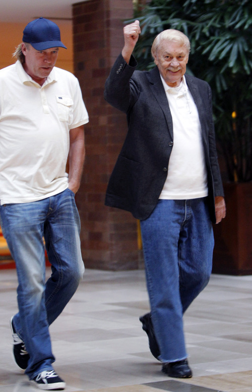 FILE - In this Sept. 15, 2011 file photo, Los Angeles Lakers owner Jerry Buss, right, gives a thumbs up as he walks with his son Jimmy Buss after the NBA basketball team owners meeting in Dallas. Buss, the Lakers' playboy owner who shepherded the NBA franchise to 10 championships, has died. He was 80. Bob Steiner, an assistant to Buss, confirmed Monday, Feb. 18, 2013  that Buss had died in Los Angeles. Further details were not available. (AP Photo/LM Otero, File)