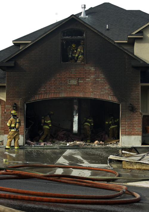 Kim Raff  |  The Salt Lake Tribune Firefighters work to put out a fire at 3664 West New Heritage Circle in West Jordan on February 18, 2012.