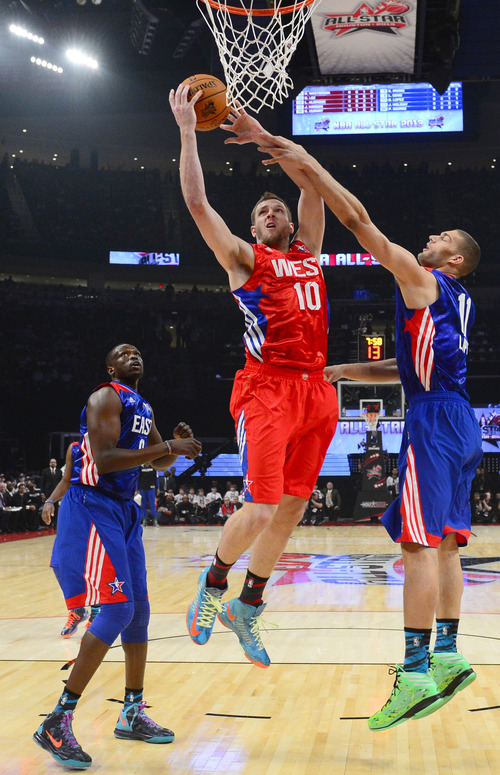 West Team's David Lee of the Golden State Warriors defended by East Team's Jrue Holiday of the Philadelphia 76ers during the first half of the NBA All-Star basketball game Sunday, Feb. 17, 2013, in Houston. (AP Photo/Bob Donnan, Pool)