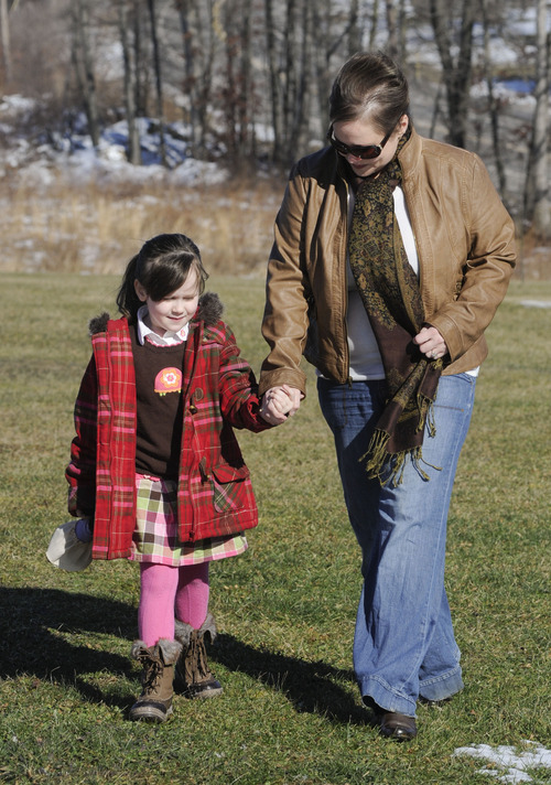 """In this Feb. 10, 2013 photo, Kelly Guarna and her 5-year-old daughter Madison walk after sitting for a portrait in Mount Carmel, Pa. The kindergartener was suspended from school for making a """"terroristic threat"""" last month after her mother said she talked about shooting a Hello Kitty bubble gun. (AP Photo/Jimmy May)"""