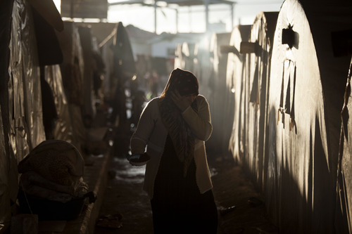 A Syrian refugee woman is seen between a line of tents in a refugee camp near Azaz, north of Aleppo province, Syria, Sunday, Feb 17, 2013. (AP Photo / Manu Brabo)